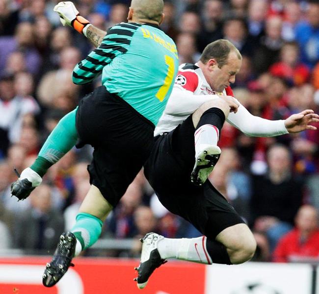 Victor Valdés choca con Wayne Rooney. EFE