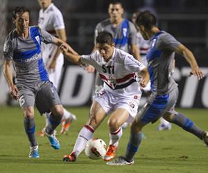 El jugador Osvaldo (c) de Sao Paulo de Brasil disputa el balón con Michael Ríos (i) y Rhodolfo (d)de Universidad Católica. EFE