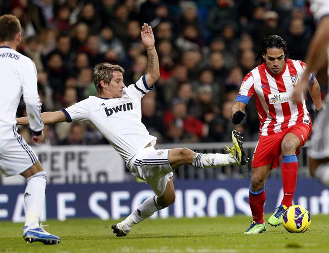 El defensa portugués del Real Madrid, Fábio Coentrão (c), intenta robar la pelota al delantero colombiano Falcao García. Foto: EFE