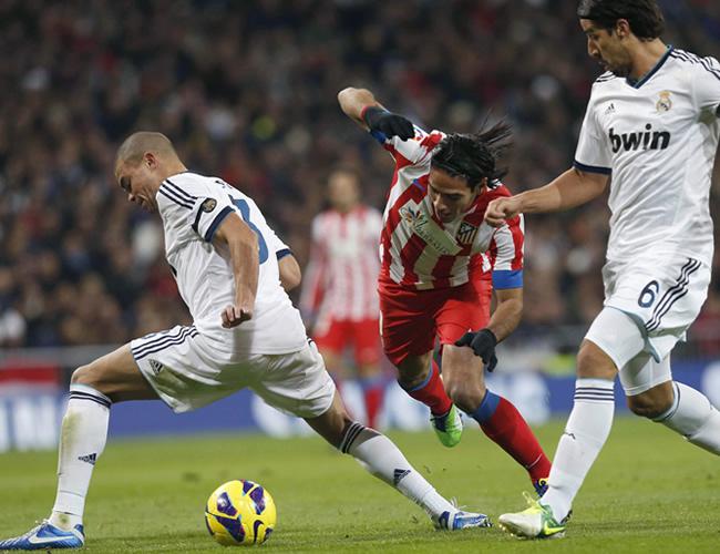 El delantero colombiano del Atlético de Madrid, Radamel Falcao (c), intenta marcharse del defensa portugués del Real Madrid, Pepe. Foto: EFE