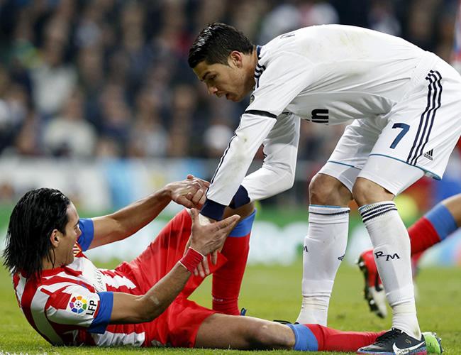 El delantero portugués del Real Madrid, Cristiano Ronaldo (d), ayuda a levantarse al delantero colombiano del Atlético de Madrid, Radamel Falcao. Foto: EFE
