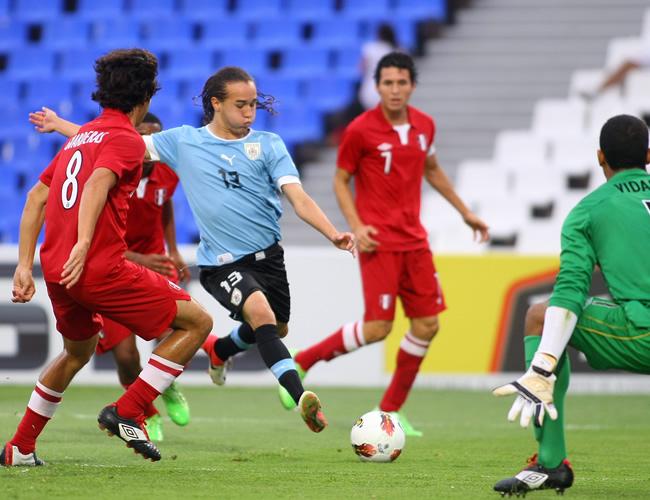 Guillermo Laxalt (2i) de Uruguay en acción ante Rafael Guarderas (d) de Perú. Foto: EFE