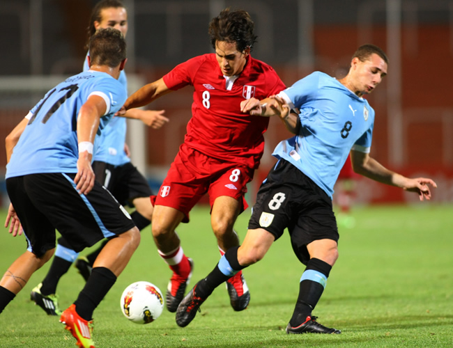 Rafael Guarderas (c) de Perú en acción ante Uruguay. Foto: EFE