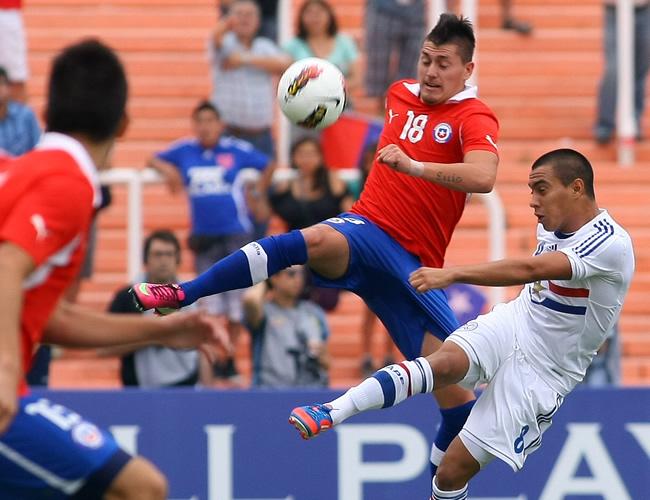 Nicolás Castillo (c) de Chile disputa el balón con Angel Cardozo Lucena de Paraguay (d). Foto: EFE