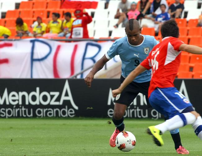 El jugador de Uruguay Diego Rolan (i) intenta pasar a un rival de Chile. Foto: EFE