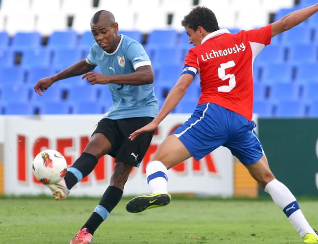 El jugador de Uruguay Diego Rolán (i) disputa un balón contra Igor Lichnovsky (d) de Chile. Foto: EFE