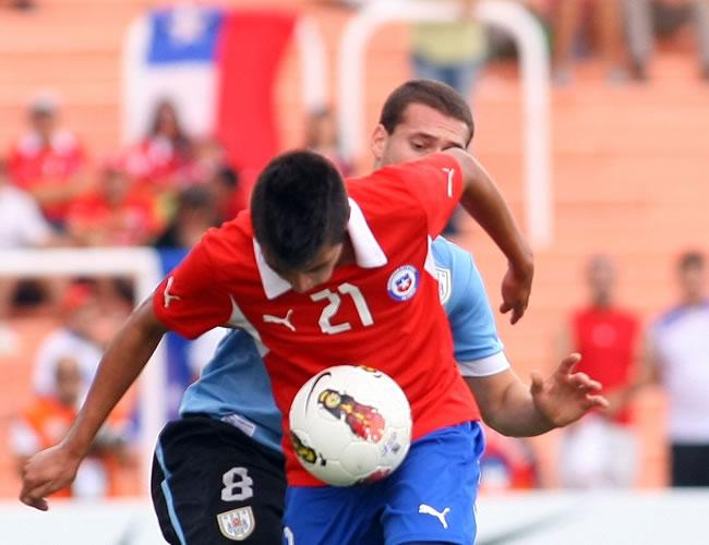 El jugador de Uruguay Sebastián Cristóforo (atrás) disputa un balón contra Ignacio Caroca (frente) de Chile. Foto: EFE
