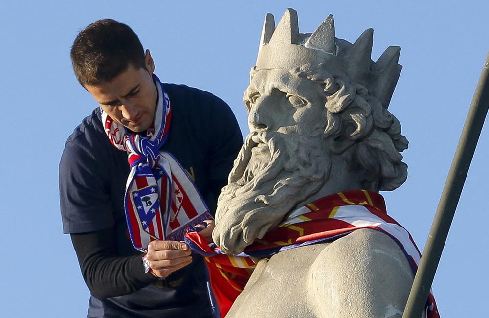 El capitán del Atlético de Madrid, Gabriel Fernández, coloca la bandera rojiblanca en el dios del mar, esta tarde en la madrileña plaza de Neptuno. Foto: EFE