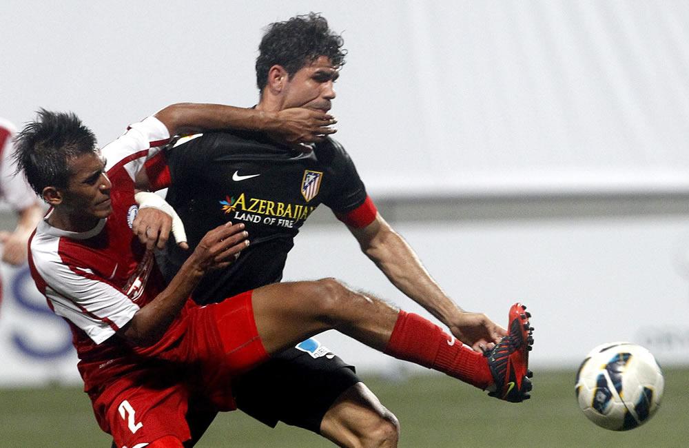 El delantero brasileño del Atlético de Madrid, Diego Costa (d) lucha por el balón con Shakir Hamzah (i) de la selección de la Liga de Singapur. Foto: EFE