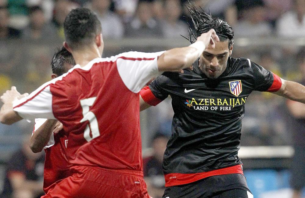 El delantero colombiano del Atlético de Madrid, Radamel Falcao (d) controla el balón frente a uno de los integrantes de una selección de la Liga de Singapur. Foto: EFE