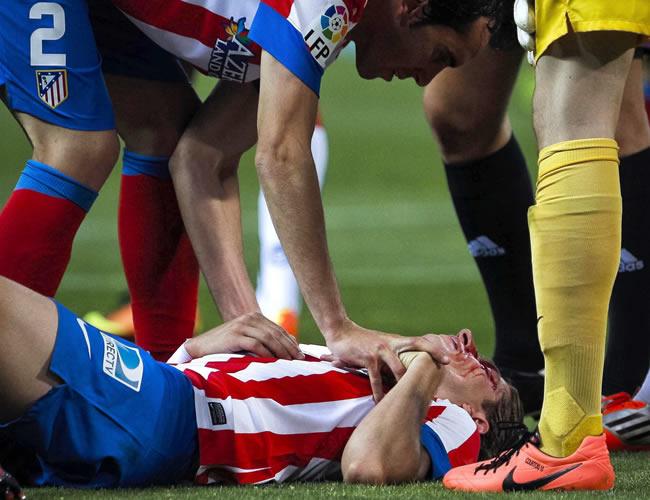 El defensa brasileño del Atlético de Madrid, Filipe Luis, en el suelo tras recibir un rodillazo en la cabeza durante el partido. Foto: EFE