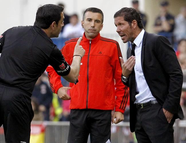 El árbitro Teixeira Vitienes (i) habla con el entrenador del Atlético de Madrid, Diego Pablo Simeone (d). Foto: EFE