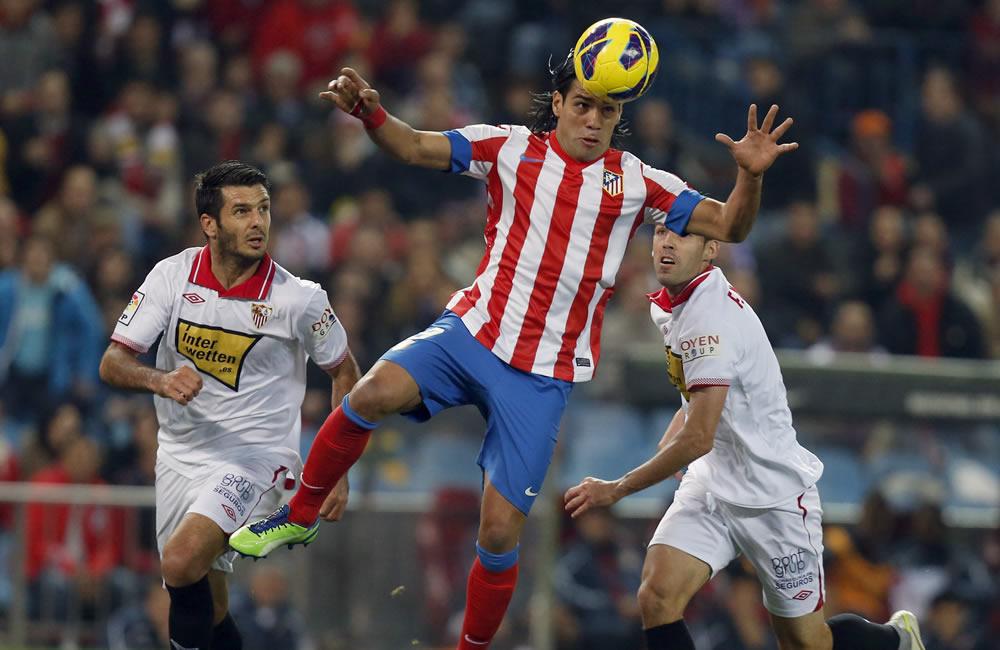 El delantero colombiano del Atlético de Madrid Radamel Falcao (c) cabecea el balón en el área contra Sevilla. Foto: EFE