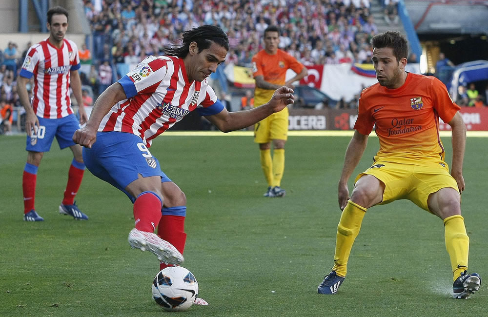 El delantero colombiano del Atlético de Madrid, Radamel Falcao (i) pelea un balón con el defensa del Barcelona Jordi Alba. Foto: EFE