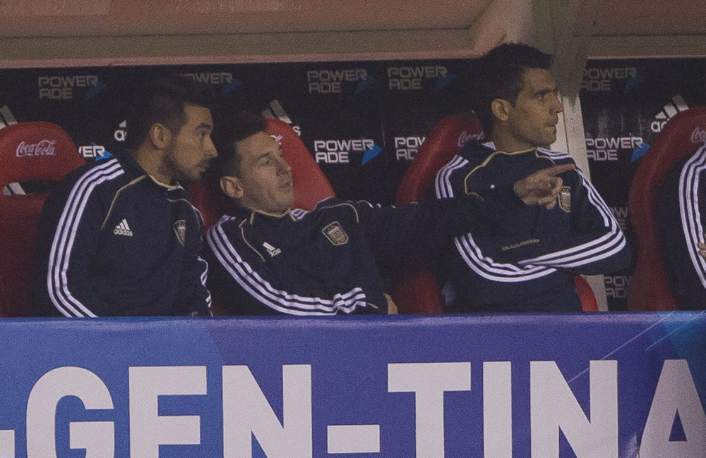 Los jugadores argentinos Ezequiel Lavezzi (i) y Lionel Messi (c) observan desde el banco. Foto: EFE