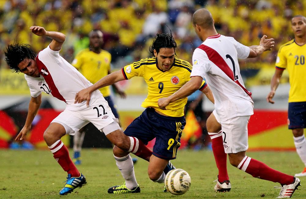 El jugador colombiano Radamel Falcao García (c) disputa el balón con los peruanos Edwin Retamoso. Foto: EFE