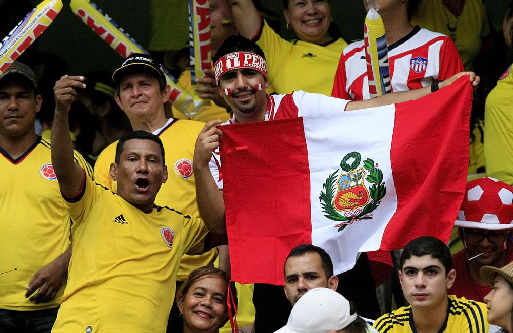 Aficionados de la selección colombiana de fútbol apoyan a su equipo junto a aficionados de la selección peruana. Foto: EFE