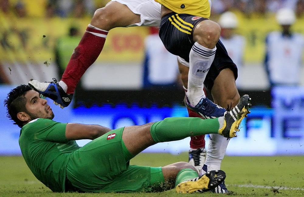El jugador colombiano Teófilo Gutiérrez (d) anota un gol ante el portero peruano Raúl Fernández. Foto: EFE