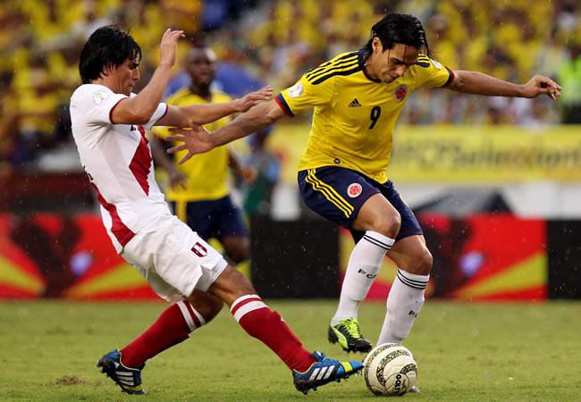 El jugador colombiano Radamel Falcao García (d) disputa el balón con el peruano Edwin Retamoso (i). Foto: EFE