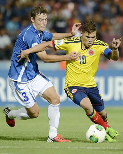 Juan Fernando Quintero (d) de Colombia con el balón ante el salvadoreño Tomas Granitto. EFE