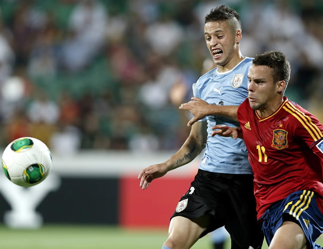 Juan Bernat (d) de España, lucha por el balón con el uruguayo Nicolás López. EFE