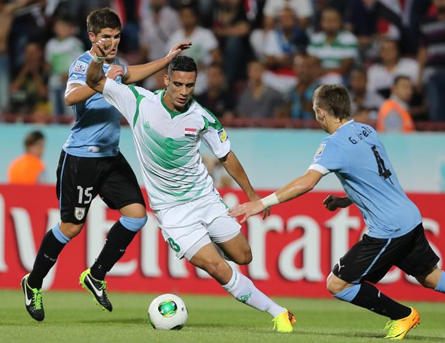 El uruguayo Guillermo Varela (d) disputa un balón con el iraquí Ali Adnan (c). EFE