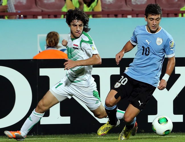 El jugador uruguayo Giorgian De Arrascaeta (d) pelea por el balón con el iraquí Humam Tareq (i). EFE