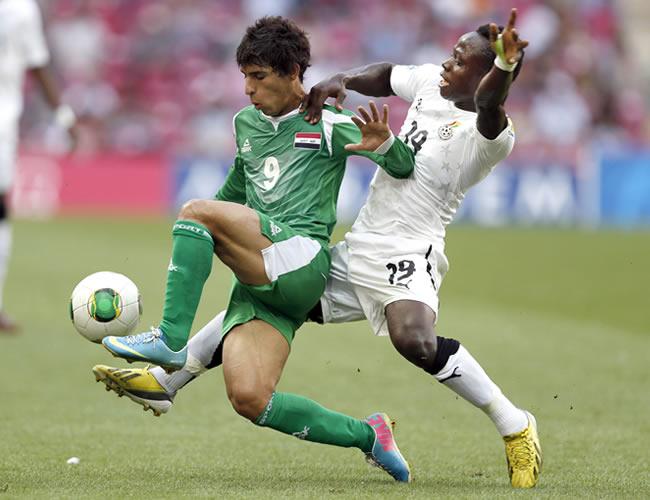 Mahdi Kamil (i) de Irak disputa el balón con Lawrence Lartey (d) de Ghana. EFE