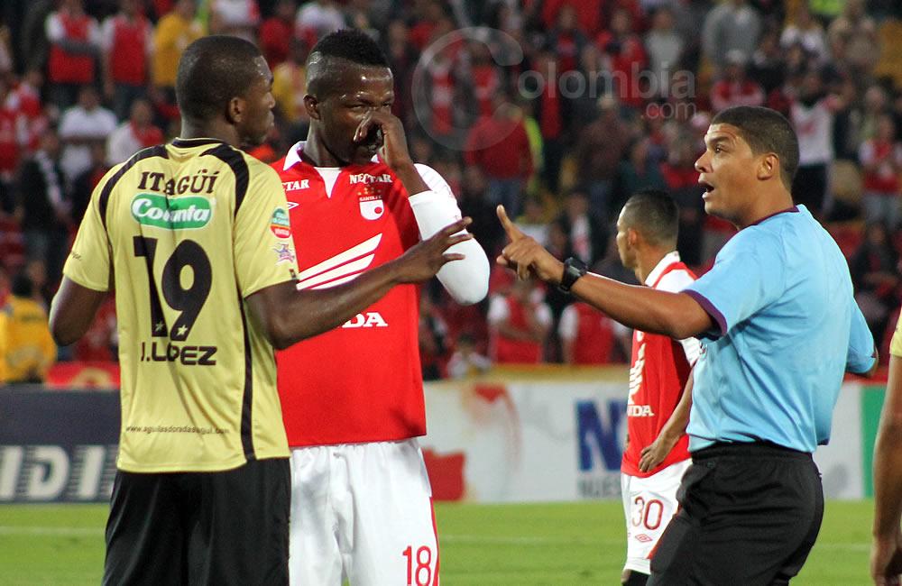 El árbitro Juan Pontón (d) advierte a Javier López de Itagüí (19) y Juián Quiñonez (c) de Santa Fe, antes de un tiro de esquina. Foto: Interlatin
