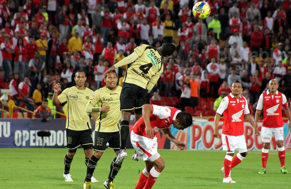 El defensa de Itagüí, Carlos Arboleda (4) gana el salto al argentino Silvio González de Independiente Santa Fe (abajo). Foto: Interlatin
