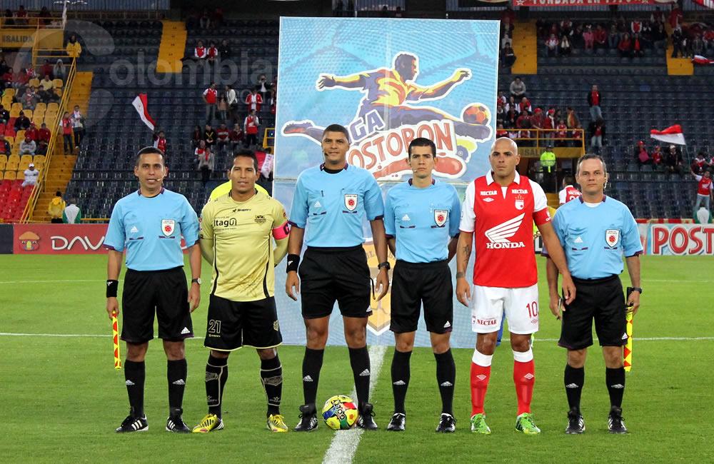 Los capitanes de Itagüí, John Javier Restrepo (i) y de Independiente Santa Fe, Omar Pérez (d), posan con los árbitros del partido. Foto: Interlatin