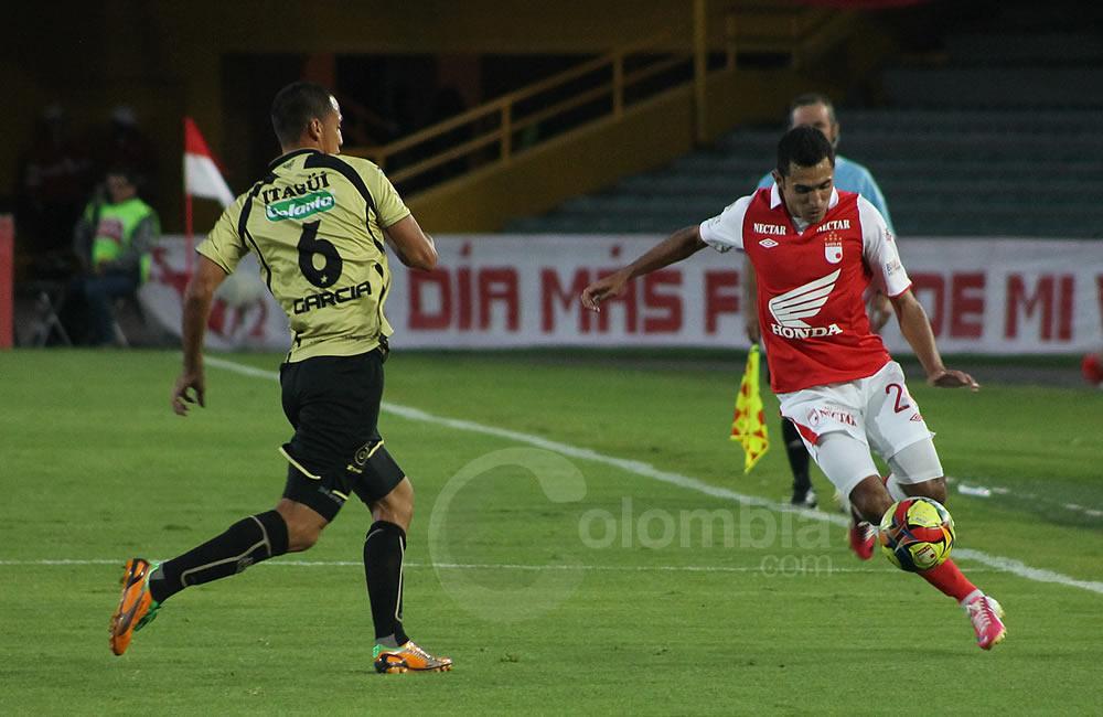 El lateral de Independiente Santa Fe, Hugo Acosta (d), avanza con el balón ante Braynner García de Itagüí (i). Foto: Interlatin