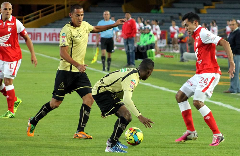 El lateral de Independiente Santa Fe, Hugo Acosta, disputa el balón ante los defensas de Itagüí. Foto: Interlatin