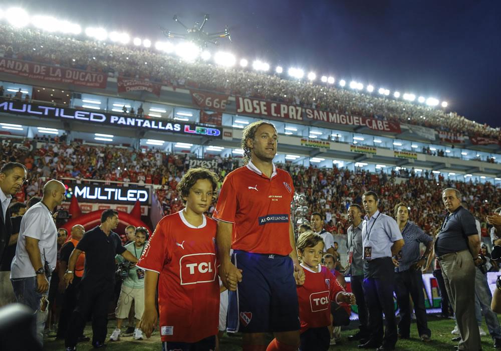 Gabriel Milito (c) sale a la cancha junto a sus hijos Santiago (i) y Lucas (d). Foto: EFE