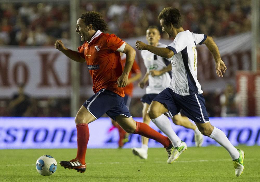 Gabriel Milito (i) corre con el balón, durante su partido de despedida. Foto: EFE