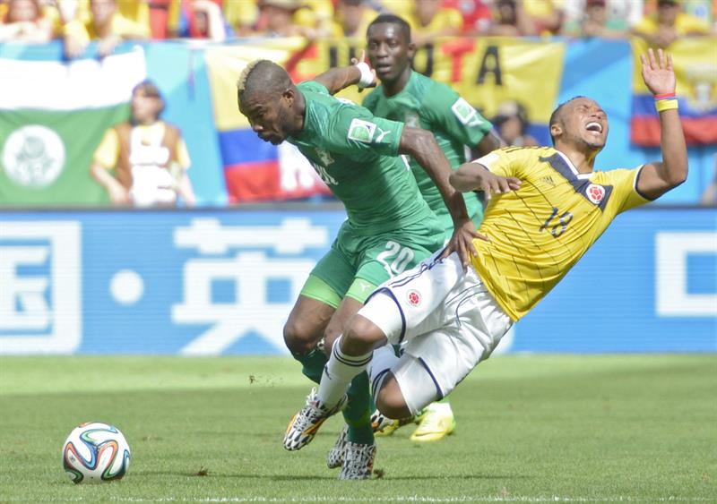 Ivory Coast's Die Serey (L) and Colombia's Juan Zuniga (R) vie for the ball on the pitch during FIFA World Cup 2014