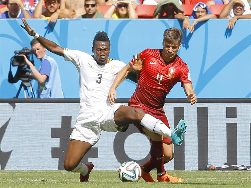 Asamoah Gyan (L) of Ghana in action with Miguel Veloso of Portugal during the FIFA World Cup 2014 group G. Foto: EFE