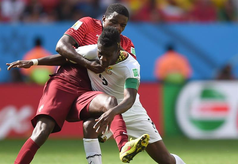 Asamoah Gyan (R) of Ghana in action against William (L) of Portugal during the FIFA World Cup 2014 group G. Foto: EFE
