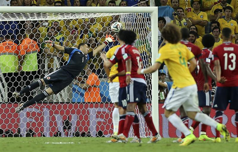 El guardameta colombiano David Ospina (i) no consigue detener el lanzamiento de falta del defensa brasileño David Luiz (d, de espaldas). Foto: EFE