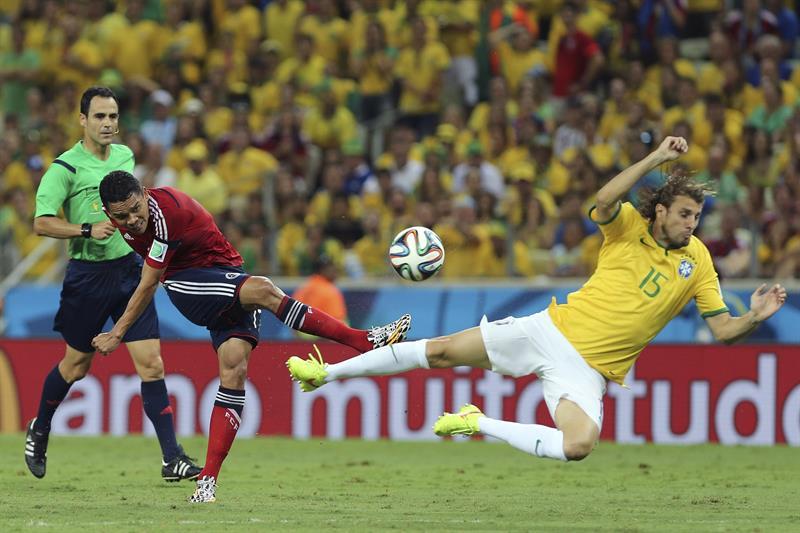 El delantero colombiano Carlos Bacca (i) lanza ante el defensa brasileño Henrique (d). Foto: EFE
