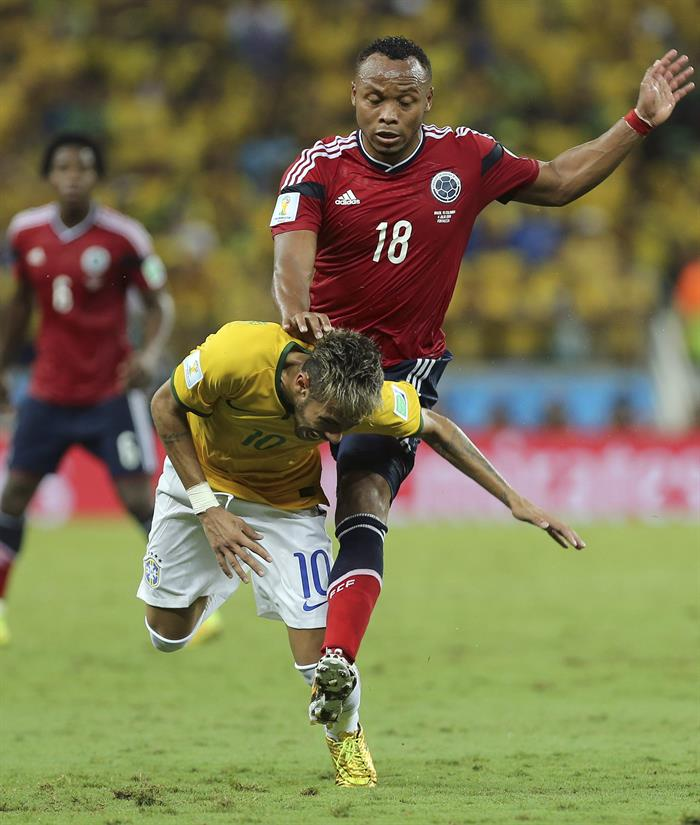 El delantero brasileño Neymar (i) cae ante el defensa colombiano Juan Zúñiga. Foto: EFE