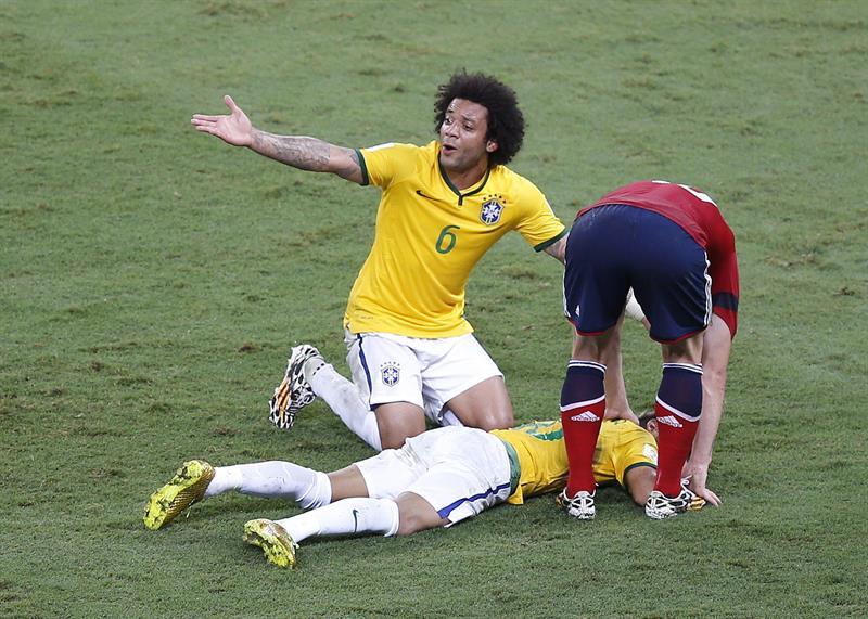 El defensa brasileño Marcelo (i) pide la asistencia para su compañero Neymar que permanece tendido en el suelo tras recibir un fuerte golpe en la espalda. Foto: EFE