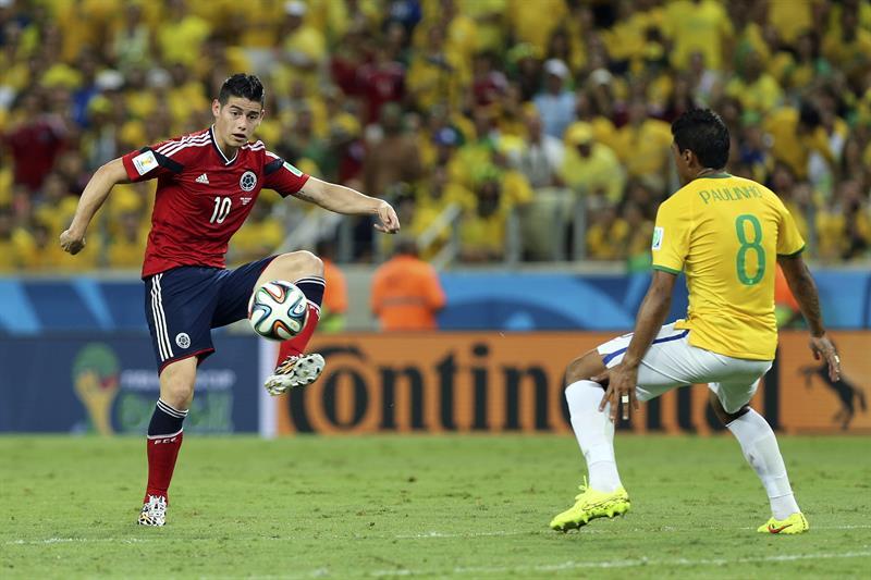 El centrocampista colombiano James Rodríguez (i) controla el balón ante el centrocampista brasileño Paulinho. Foto: EFE