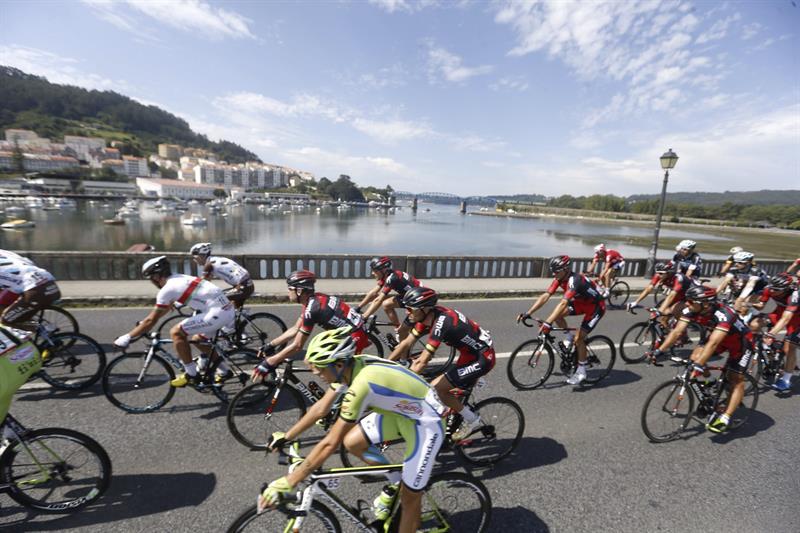 El pelotón a su paso por Pontedeume, durante la decimoséptima etapa de la Vuelta. EFE