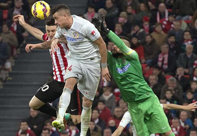 El delantero del Athletic Aduriz (i) salta a por un balón con Giménez (c) ante el portero Moyá, ambos del Atlético de Madrid. Foto: EFE