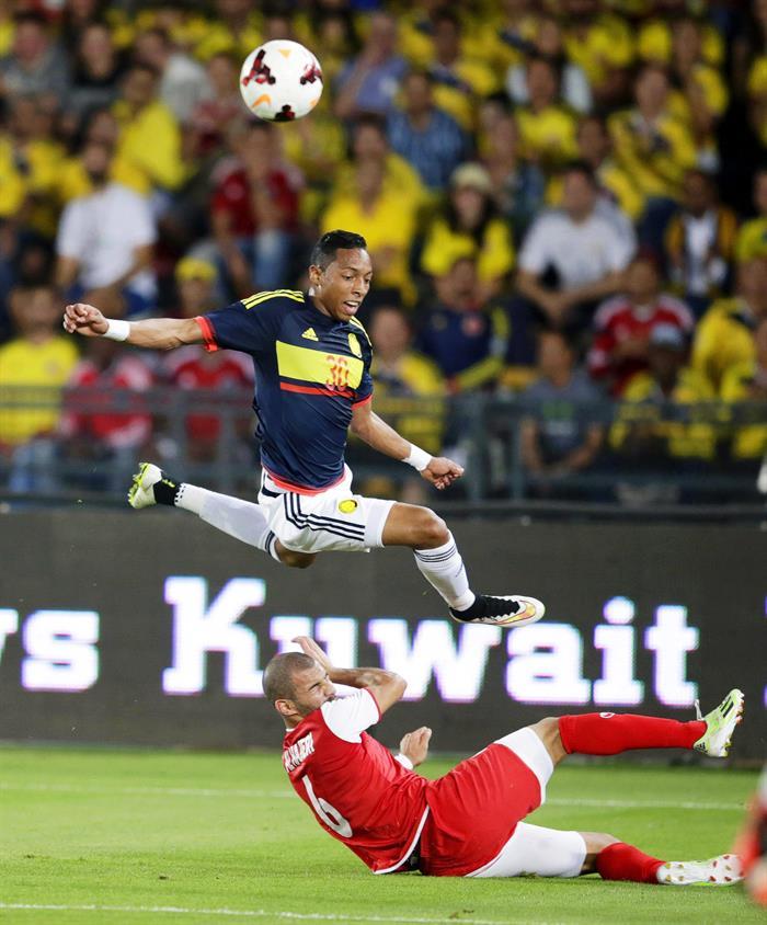 El defensa de la selección colombiana, Johan Mojica (arriba) lucha por el balón con Fahad Al-Hajeri (abajo) de Kuwait durante el partido. Foto: EFE