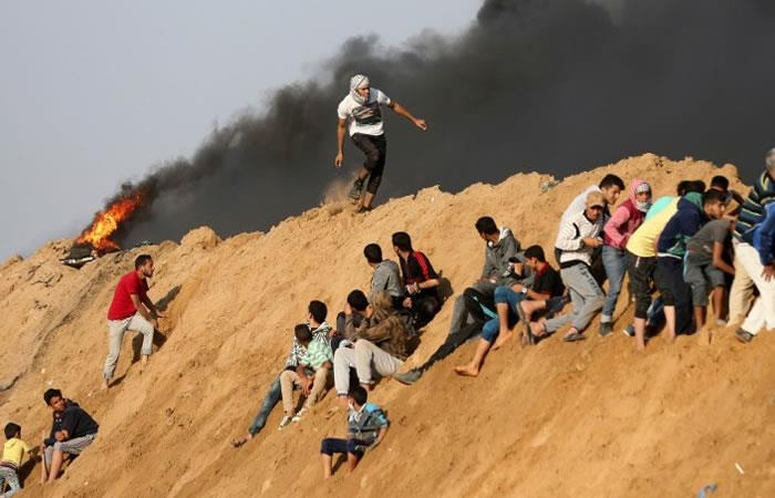 Manifestantes palestinos se protegen ante los disparos de la policía de Israel. Foto: AFP