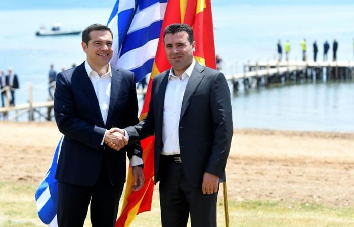 El primer ministro griego, Alexis Tsipras (izq), y su homólogo macedonio, Zoran Zaev, se dan la mano a orillas del lago Prespa, fronterizo entra ambos países. Foto: AFP