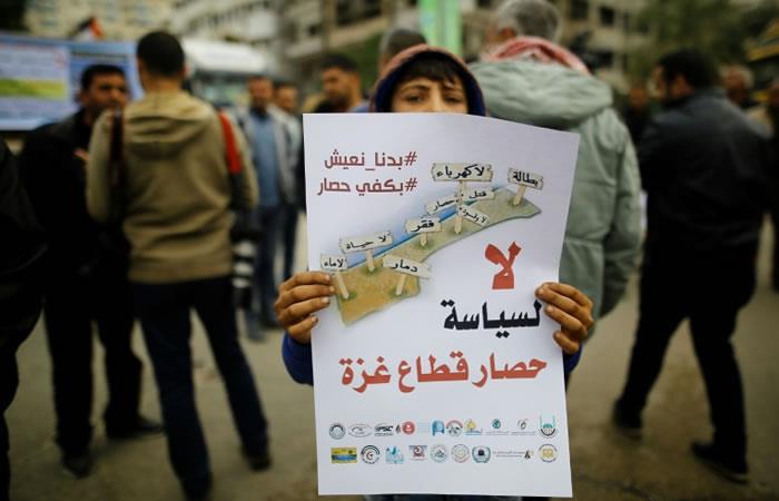 Un niño palestino sostiene un cartel durante una protesta contra el bloqueo y asedio de Israel a la Franja de Gaza. Foto: AFP
