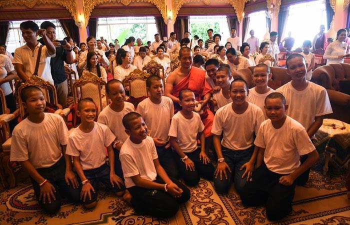 """El DT Ekkapol Chantawong (C) y los doce jugadores de los """"Jabalíes Salvajes"""", durante la ceremonia posterior al retiro espiritual que realizaron en homenaje al buzo fallecido. Foto: AFP"""